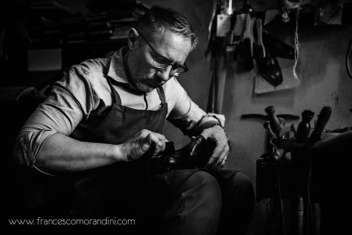 Roberto Ugolini, storia di un artigiano fiorentino. | Dedizione nella pulizia delle scarpe da parte del calzolaio in bianco e nero
